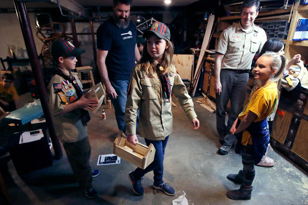 """Tatum Weir, center, carries a tool box she built as her twin brother Ian, left, follows after a Cub Scout meeting in Madbury, N.H. With girls soon entering the ranks, the BSA says that iconic name will change to """"Scouts BSA."""" The change will take effect in February 2019. (Charles Krupa/AP File)"""
