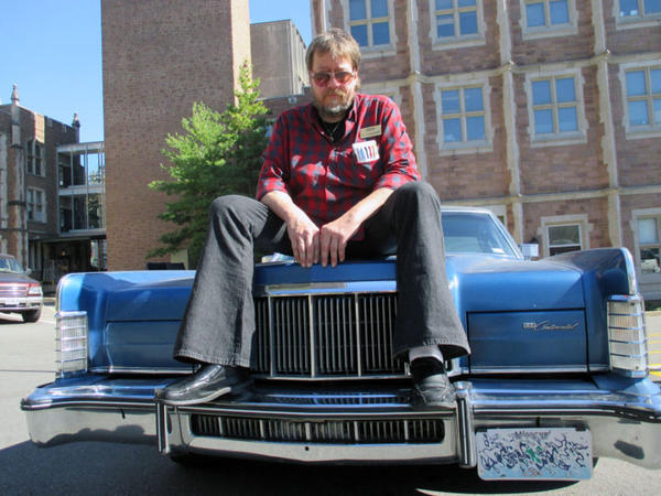 Gerry Rohde sitting on one of his classic cars in a parking lot at Washington University. Note his St. Louis Public Radio nametag on his shirt.
