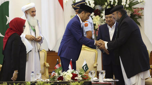 Scholars from Afghanistan, Pakistan and Indonesia attended a conference on Friday to discuss stability in Afghanistan. Indonesian President Joko Widodo (center) shakes hands with Qibla Ayaz, chairman of Pakistan's Council of Islamic Ideology.