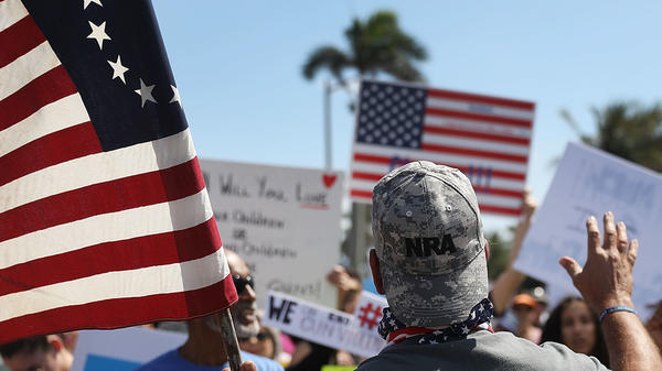 A man in an NRA hat (who didn't want to give his name) speaks at a March For Our Lives event on March 24 in West Palm Beach, Fla.
