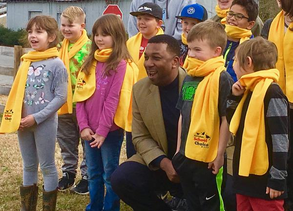 Students at Yadkin Valley Community School, a private Montessori School in Elkin, crowd around school choice advocate Darrell Allison in celebration of National School Choice Week. A number of the school's students receive vouchers for tuition assistance.