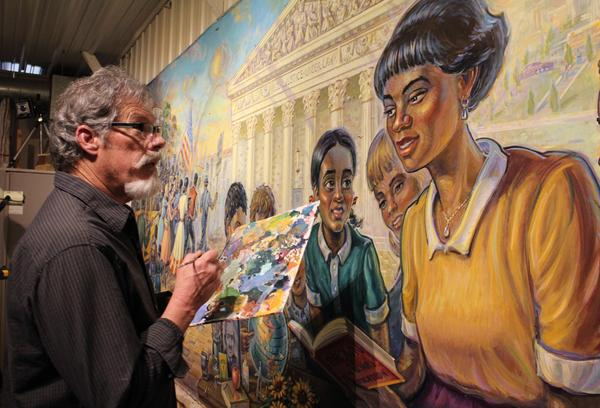 Artist Michael Young adds the finishing touches to the Brown v. Board of Education Mural in his studio in Kansas City, Kansas. Young says it's a dream come true to paint the mural, which visitors can see on display at the Kansas Capitol for years to come.