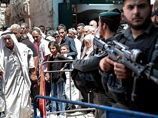 Israeli police stand guard in the main street of the Muslim Quarter of Jerusalem's Old City after Palestinian worshippers at Al-Aqsa Mosque took part in the first Friday prayers of the holy month of Ramadan.