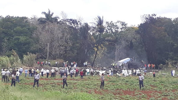 First responders and law enforcement gather in the field where an airliner crashed after takeoff Friday, just outside the international airport in Havana, Cuba.
