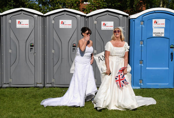 Two brides — at least in dress — pause outside the port-a-potties set up for the Windsor Castle crowd.