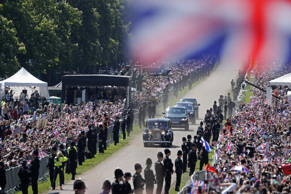 The Windsor Castle crowds and the millions watching at home get their first glimpse of Meghan Markle as she is driven to the chapel.