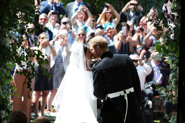 The Duchess and Duke of Sussex kiss on the steps of St. George's Chapel in Windsor Castle to the cheers of the crowd gathered outside.