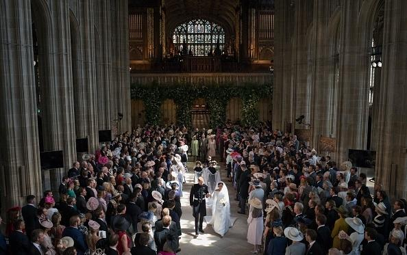 Harry and Meghan proceed out of St. George's Chapel after the wedding, followed by their young bridesmaids and page boys and their family.