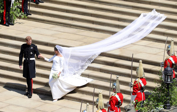 Prince Harry escorts the newest member of the royal family outside St. George's Chapel. Meghan's dress was designed by Clare Waight Keller.