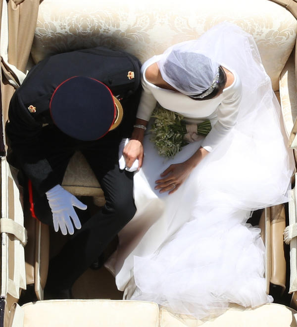 Harry and Megan hold hands in the Ascot Landau Carriage as their carriage procession rides along the Long Walk after their wedding ceremony.