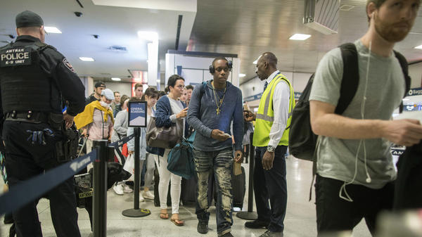 An Amtrak police officer with a bomb sniffing dog watches as people board a train en route to Boston at New York's Penn Station, as travelers set out for the long Memorial Day weekend on Friday.