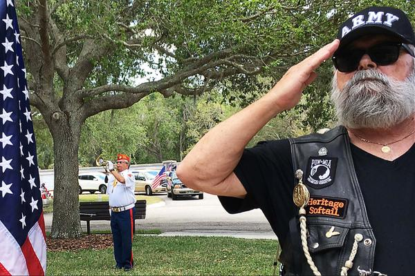 A bugler plays Taps at Bay Pines National Cemetery as veterans stand at attention for their fellow former service members who died without close relatives.