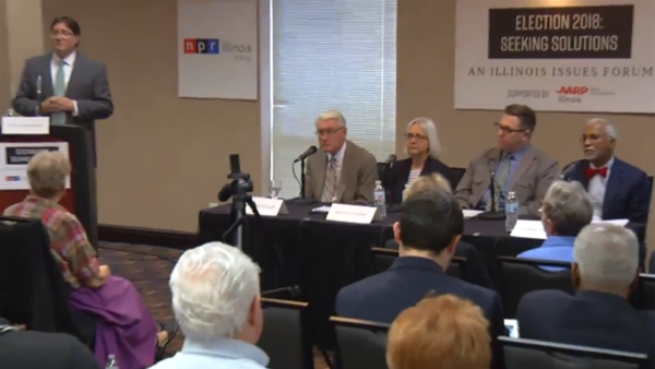 Sean Crawford (standing) and the panel: (left to right) Jim Edgar, Beverly Bunch, Brian Mackey, and Donne Trotter listen to an audience question at the 2018 Illinois Issues Forum seeking solutions for the state's fiscal health.