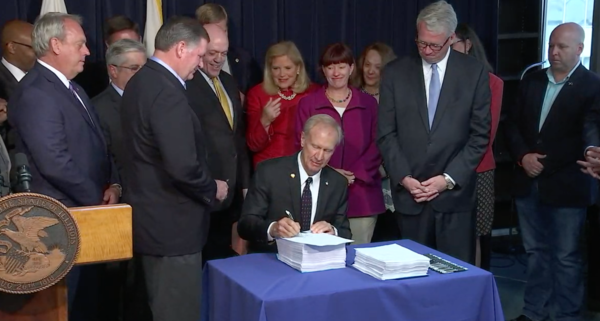 Gov. Bruce Rauner signs the FY2019 budget, surrounded by the Democratic and Republican legislators who negotiated it, at the James R. Thompson Center in Chicago.