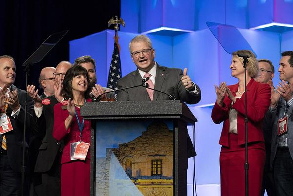 James Dickey stands with supporters after being re-elected chairman of the Texas Republican Party.