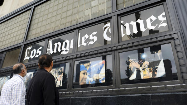 Pedestrians look at news photos posted outside the Los Angeles Times building in downtown Los Angeles. Pharmaceuticals billionaire Dr. Patrick Soon-Shiong will take over the <em>LA Times </em>on Monday.
