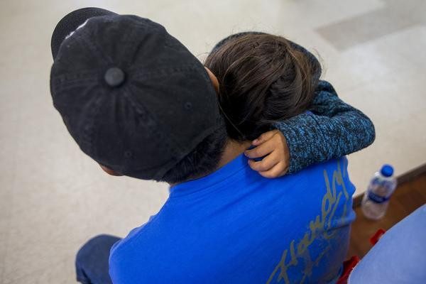 A young migrant family waits for the arrangements for their bus at Catholic Charities in McAllen, Texas. (Jesse Costa/WBUR)
