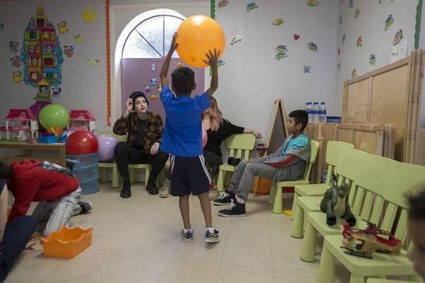 A young boy plays with a ball with volunteers at Catholic Charities in McAllen, Texas. (Jesse Costa/WBUR)
