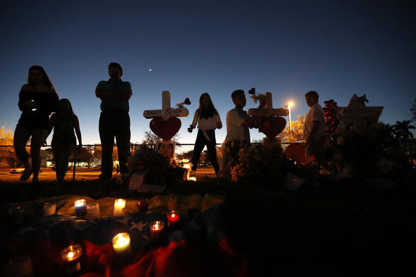 People visit a makeshift memorial outside Marjory Stoneman Douglas High School in Parkland, Fla., where 17 students and faculty were killed in a mass shooting on Feb. 14.