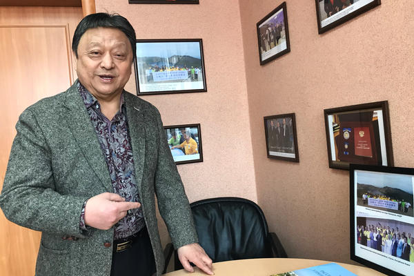 Valentin Pak, a Russian entrepreneur and leader of Vladivostok's ethnic Korean community, shows photos in his office in the Russian Pacific coast city.