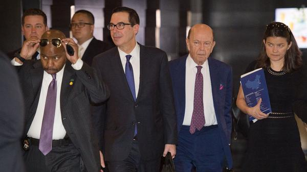 """Treasury Secretary Steven Mnuchin (center left) and Commerce Secretary Wilbur Ross (center right) walk through a hotel lobby as they head to a state guest house to meet Chinese officials in Beijing on Friday. The talks included a """"thorough exchange of views,"""" Chinese media report."""