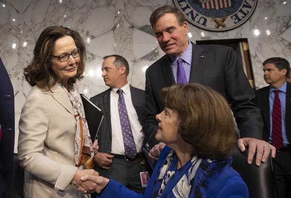 Gina Haspel (in white), the nominee to lead the CIA, is welcomed at her confirmation hearing before the Senate intelligence committee by Sen. Dianne Feinstein, D-Calif. (seated), and Vice Chairman Mark Warner, D-Va., in Washington on May 9. The committee voted 10-5 on Wednesday to recommend Haspel's confirmation by the full Senate.