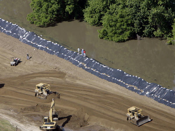 Crews push extra sand onto Mississippi River levees in the Sny drainage district in Illinois during a flood in June 2008.