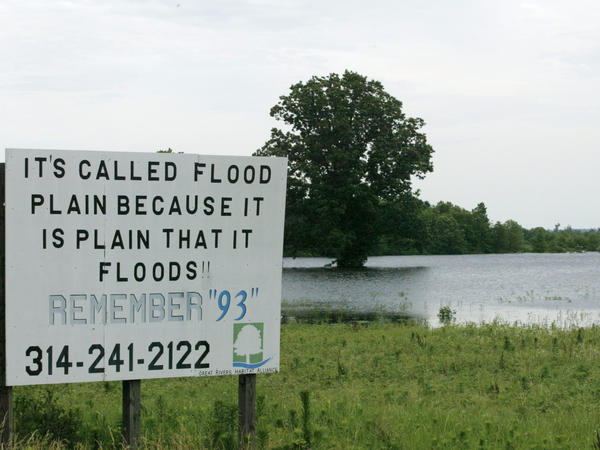 A sign in a field near Winfield, Mo., during a Mississippi River flood in 2008. The area suffered a similarly serious flood in 1993. The frequency of severity of flooding up and down the river have increased due to climate change and river control structures such as levees.