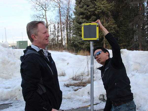 Brian Shumaker, right, and a colleague with Beaded Stream adjust a solar powered data logger. It transmits precise temperatures so oil companies know when the tundra is frozen enough to operate.