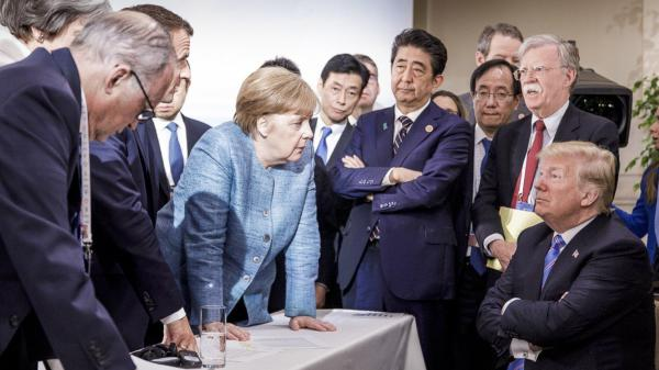 In this photo made available by the German Federal Government, German Chancellor Angela Merkel, center, speaks with President Trump, seated at right, during the G-7 Leaders Summit in La Malbaie, Quebec, Canada, on Saturday, June 9.