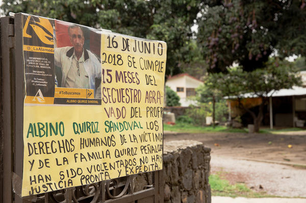 "A sign at the front of Quiroz's home reads: ""June 16, 2018, 15 months since the aggravated kidnapping of Professor Albino Quiroz Sandoval. The human rights of the victim and the family have been violated. There is no prompt and expeditious justice."""