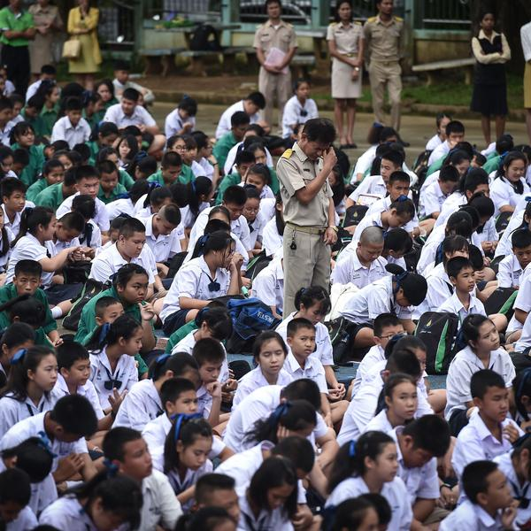 Thai schoolchildren and their teachers pray on Monday for classmates who went missing June 23 inside the Tham Luang Nang Non cave in Chiang Rai.