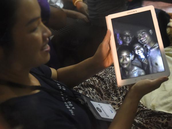 A happy family member shows the latest pictures of the missing boys taken by rescue divers inside Tham Luang cave when all members of children's soccer team and their coach were found alive on Monday.