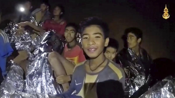 Thai boys smile as a medic treats scratches on one of the children trapped inside a cave in northern Thailand.