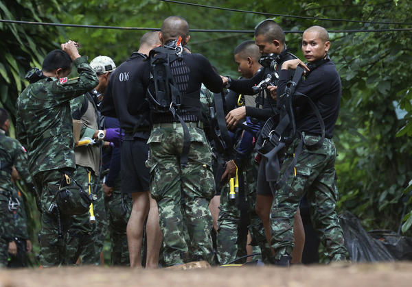 Rescuers prepare dive gear on Wednesday at the entrance of a cave complex  where 12 boys and their soccer coach are trapped in northern Thailand.