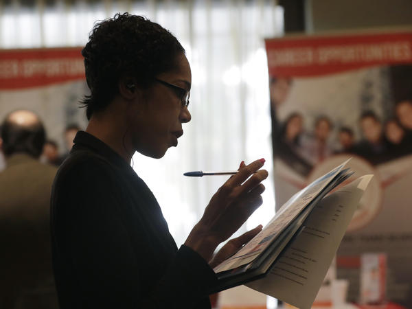 Joana Dudley looks at a list of job prospects at a job fair in Miami Lakes, Fla., in January. In the government's June jobs report, the unemployment rate ticked up to 4 percent with more people entering the labor force.