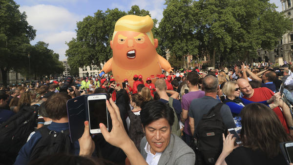 """A protest against President Trump in London's Parliament Square includes a giant balloon of """"Trump Baby"""" in a diaper on Friday. It flew high above the statutes of prominent historical figures including Winston Churchill, Mahatma Gandhi and Millicent Fawcett."""