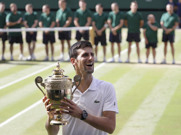 Serbia's Novak Djokovic beamed as he held his trophy, having defeated South Africa's Kevin Anderson to win his fourth Wimbledon.