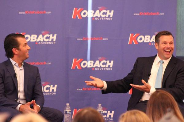 Donald Trump Jr., left, and Kris Kobach talk on stage at Tuesday's event in Wichita.