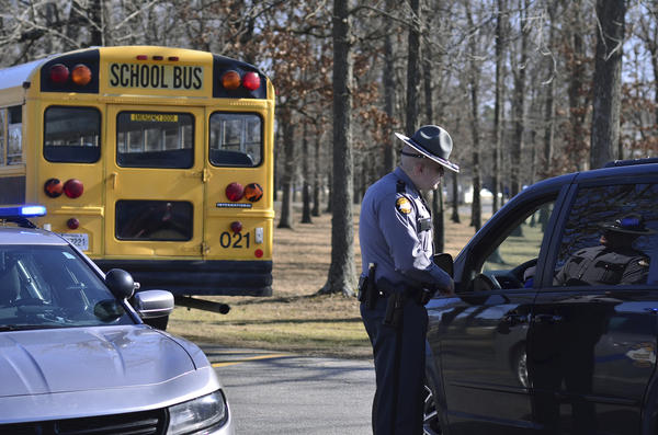 A Kentucky State Police trooper checks with a motorist entering Marshall County High School Wednesday, Jan. 24, 2018, near Benton, Ky. Two students died and another 18 people were injured in a shooting the day before.