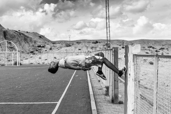 Boy back flips off a wall in a soccer field, Umm-Al-Arais