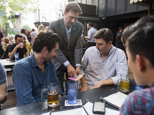 Texas Attorney General candidate Justin Nelson shows, from left, Zack Tavel and Mark Donnelly a map of gerrymander-ed congressional districts in Austin at Easy Tiger bar in Congressional District 21 as part of a pub crawl across three congressional districts in downtown Austin - the Pub Crawl to End Gerrymandering.