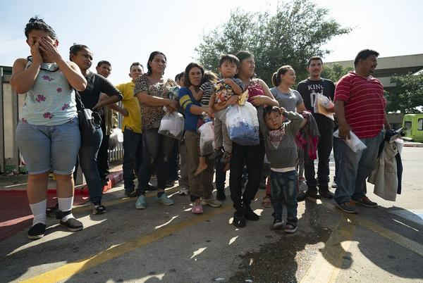 Immigrants, many wearing ankle monitors, are dropped off last month at the McAllen Central Station, where they are given bus tickets to other parts of the country.