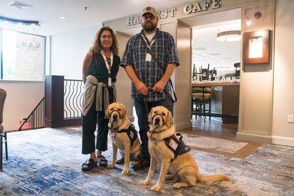Gina Esoldi stands with her service dog Ricky along with Kyle Santiago with his dog Kassi. Both work with Next Step Service Dogs.