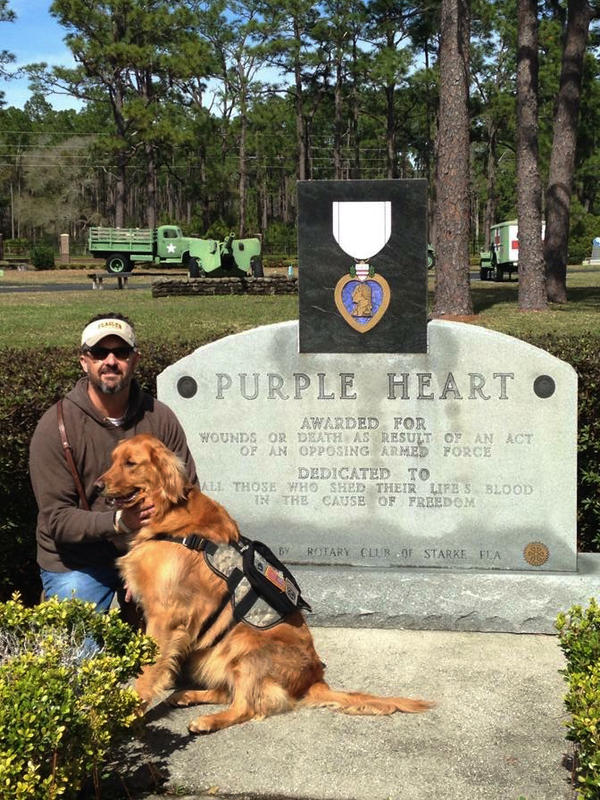 Retired Army Sgt. Kevin Crowell sits with Bella, his psychiatric service dog.