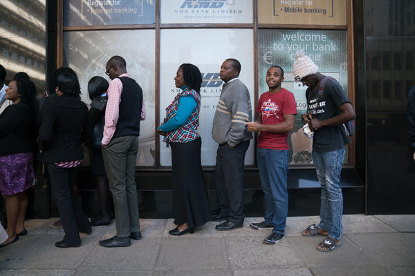 Zimbabweans stand in line in front of NMB bank in Harare. Zimbabwe has been facing a major cash shortage for the past two years, a symptom of the country's larger and longer economic crisis.