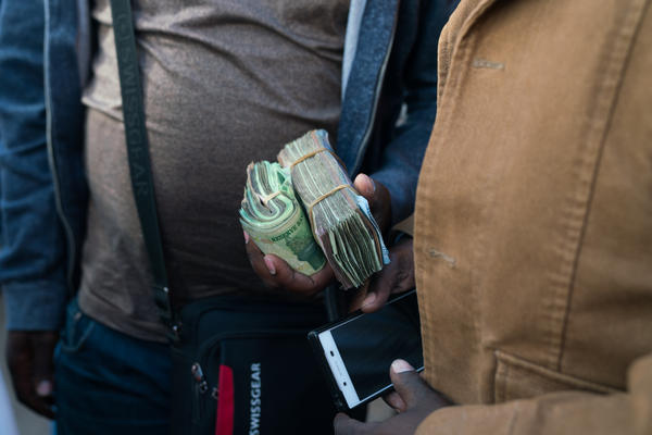 A money trader holds wads of cash on the street in Harare.