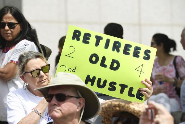 Yvonne Landin, a retired teacher from Corpus Christi, holds a sign as retired teachers gather at the Teacher Retirement building in Austin on Thursday.