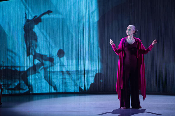 """In <em>As I Remember It</em>, <a href=""""http://www.carmendelavallade.com/"""" target=""""_blank"""">Carmen de Lavallade</a> watches footage of herself dancing in old movies projected on a large screen behind her."""