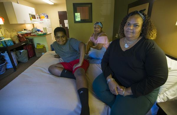 Lisbeth Sandoval, (far right), her daughter, Sheylibeth, and her son, Stephen, inside a hotel room in Lowell. (Jesse Costa/WBUR)